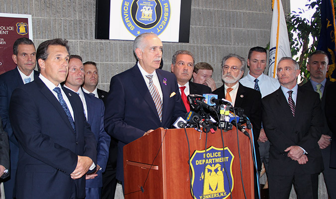 man at podium with men standing behind him